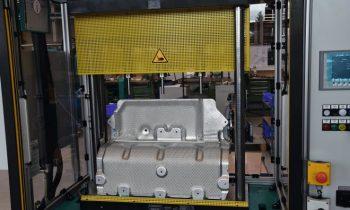 Das Hitzeschutzblech aus zwei miteinander verbundenen Alublechen; darüber ist ein Teil des Oberwerkzeugs mit den drei Stempeln zum Setzen von gleichzeitig drei Tox-Rund-Punkt-Verbindungen zu sehen. Bild: Tox